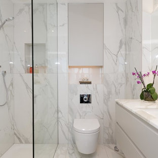 Inspiration for a medium sized contemporary shower room bathroom in London with flat-panel cabinets, white cabinets, a shower/bath combination, a wall mounted toilet, marble tiles, marble flooring, white floors, white tiles, a submerged sink, marble worktops and an open shower.