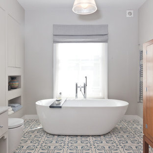 Design ideas for a classic ensuite bathroom in London with a freestanding bath and grey walls.