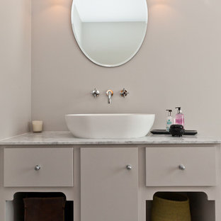 Transitional bathroom photo in London with furniture-like cabinets and a vessel sink