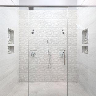 Modern inredning av ett stort en-suite badrum, med dusch med gångjärnsdörr, släta luckor, skåp i mörkt trä, ett fristående badkar, en kantlös dusch, beige kakel, porslinskakel, vita väggar, klinkergolv i porslin, ett fristående handfat, bänkskiva i kvarts och beiget golv