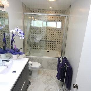 Esempio di una piccola stanza da bagno padronale minimalista con ante a filo, ante in legno bruno, vasca da incasso, vasca/doccia, WC monopezzo, piastrelle multicolore, pareti bianche, pavimento in marmo, lavabo da incasso e top in quarzite