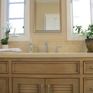 ロサンゼルスの中サイズのおしゃれなマスターバスルーム (レイズドパネル扉のキャビネット、茶色いキャビネット、一体型トイレ、ベージュの壁、磁器タイルの床、オーバーカウンターシンク、珪岩の洗面台、ベージュの床、開き戸のシャワー、ベージュのカウンター) の写真