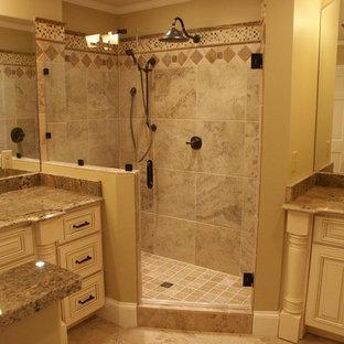 シャーロットの中サイズのトラディショナルスタイルのおしゃれなマスターバスルーム (レイズドパネル扉のキャビネット、白いキャビネット、コーナー設置型シャワー、分離型トイレ、ベージュのタイル、石タイル、ベージュの壁、ライムストーンの床、アンダーカウンター洗面器、御影石の洗面台) の写真