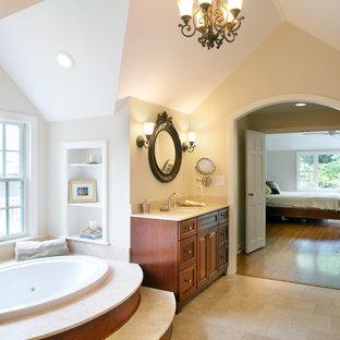 Foto di una stanza da bagno padronale classica con lavabo sottopiano, ante con riquadro incassato, ante in legno scuro, top in pietra calcarea, vasca idromassaggio, piastrelle beige, pareti beige e pavimento in gres porcellanato