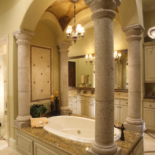 Geräumiges Mediterranes Badezimmer En Suite mit Unterbauwaschbecken, profilierten Schrankfronten, beigen Schränken, Granit-Waschbecken/Waschtisch, beigefarbenen Fliesen, Terrakottafliesen, beiger Wandfarbe und Terrakottaboden in Houston