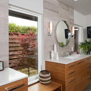 Modernes Badezimmer mit Unterbauwaschbecken, flächenbündigen Schrankfronten, hellbraunen Holzschränken und grauen Fliesen in Dallas