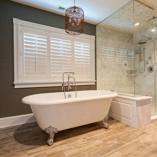 Immagine di una stanza da bagno padronale moderna di medie dimensioni con doccia ad angolo, piastrelle di marmo, pareti marroni, pavimento in legno massello medio, porta doccia a battente e vasca con piedi a zampa di leone