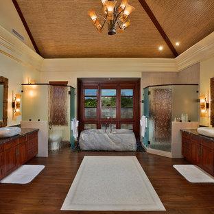 Imagen de cuarto de baño principal, asiático, grande, con lavabo sobreencimera, armarios estilo shaker, puertas de armario de madera oscura, bañera exenta, ducha esquinera, encimera de mármol, paredes amarillas y suelo de madera en tonos medios