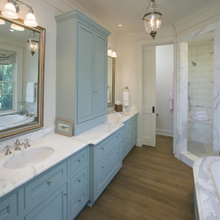 Inspiration for a traditional bathroom in Charleston with a corner shower and blue cabinets.
