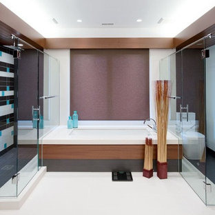 Example of a large trendy master beige tile and porcelain tile porcelain floor corner shower design in Columbus with flat-panel cabinets, medium tone wood cabinets, quartzite countertops, an undermount tub and a one-piece toilet