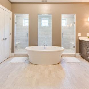 ワシントンD.C.の広いコンテンポラリースタイルのおしゃれなマスターバスルーム (落し込みパネル扉のキャビネット、濃色木目調キャビネット、置き型浴槽、洗い場付きシャワー、分離型トイレ、ベージュのタイル、ベージュの壁、セラミックタイルの床、一体型シンク、珪岩の洗面台、ベージュの床、開き戸のシャワー、白い洗面カウンター、シャワーベンチ、洗面台2つ、造り付け洗面台、格子天井) の写真