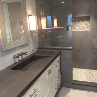 Foto di una stanza da bagno design con ante di vetro, doccia aperta, WC monopezzo, piastrelle grigie, piastrelle in gres porcellanato, pavimento con piastrelle di ciottoli, lavabo integrato e top in cemento