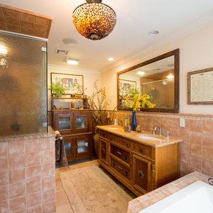Ejemplo de cuarto de baño principal, costero, grande, con armarios tipo vitrina, puertas de armario de madera oscura, encimera de granito, baldosas y/o azulejos rosa, baldosas y/o azulejos de cerámica, bañera esquinera, ducha empotrada, lavabo bajoencimera y paredes blancas