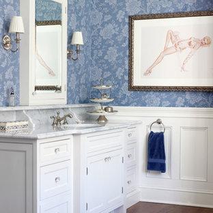 Immagine di una stanza da bagno classica con lavabo sottopiano, consolle stile comò, ante bianche, top in marmo e pareti blu