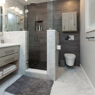 Photo of a medium sized modern ensuite bathroom in Other with distressed cabinets, a wall mounted toilet, multi-coloured tiles, porcelain tiles, grey walls, pebble tile flooring, a submerged sink and engineered stone worktops.