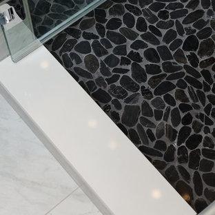 他の地域の中サイズのモダンスタイルのおしゃれなマスターバスルーム (ヴィンテージ仕上げキャビネット、壁掛け式トイレ、マルチカラーのタイル、磁器タイル、グレーの壁、玉石タイル、アンダーカウンター洗面器、クオーツストーンの洗面台) の写真