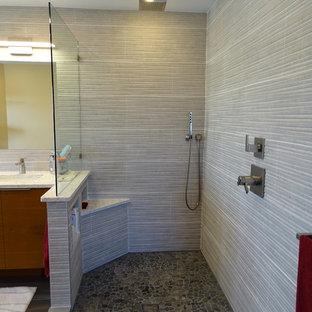 Cette image montre une salle de bain principale design de taille moyenne avec un placard à porte plane, des portes de placard en bois brun, une douche ouverte, des carreaux de porcelaine, un sol en carrelage de porcelaine, un lavabo encastré, un plan de toilette en quartz modifié, un WC à poser, un carrelage gris, un carrelage blanc et un mur jaune.