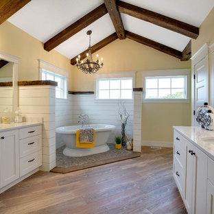 Idéer för lantliga badrum, med skåp i shakerstil, vita skåp, ett fristående badkar, brun kakel, gula väggar, ett undermonterad handfat och granitbänkskiva