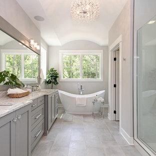 グランドラピッズのトランジショナルスタイルのおしゃれなマスターバスルーム (シェーカースタイル扉のキャビネット、グレーのキャビネット、置き型浴槽、アルコーブ型シャワー、グレーの壁、アンダーカウンター洗面器、グレーの床、開き戸のシャワー、白い洗面カウンター) の写真