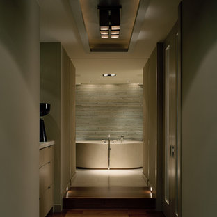 This is an example of a contemporary bathroom in Seattle with a freestanding bath and limestone tiles.