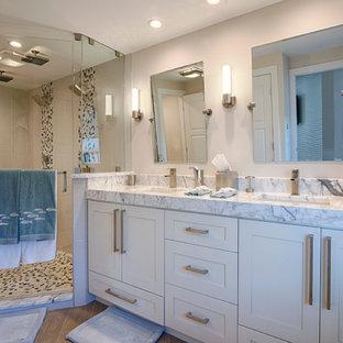 Idee per una stanza da bagno padronale design di medie dimensioni con ante bianche, doccia ad angolo, WC a due pezzi, pareti bianche, parquet chiaro, lavabo sottopiano, pavimento marrone, porta doccia a battente, ante in stile shaker, piastrelle beige, piastrelle di ciottoli e top in marmo