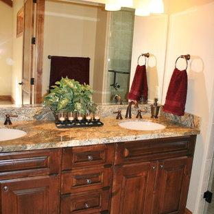 Foto de cuarto de baño rústico con lavabo bajoencimera, armarios con paneles con relieve, puertas de armario de madera oscura, encimera de vidrio, baldosas y/o azulejos beige, baldosas y/o azulejos de porcelana y suelo de baldosas de porcelana