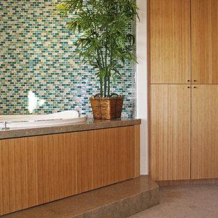 Idee per una stanza da bagno padronale minimal di medie dimensioni con lavabo a bacinella, ante lisce, ante in legno scuro, top in pietra calcarea, vasca idromassaggio, piastrelle verdi, piastrelle di vetro, pareti multicolore e pavimento in marmo