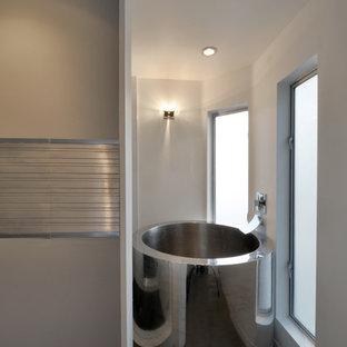 Diseño de cuarto de baño principal, minimalista, de tamaño medio, con armarios con paneles lisos, sanitario de una pieza, baldosas y/o azulejos grises, losas de piedra, paredes amarillas, suelo de baldosas de porcelana, bañera japonesa, ducha abierta, lavabo sobreencimera y encimera de cuarzo compacto