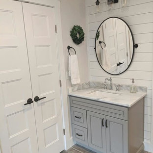Inspiration for a mid-sized country master bathroom in Raleigh with flat-panel cabinets, grey cabinets, a freestanding tub, a corner shower, gray tile, porcelain tile, grey walls, porcelain floors, an undermount sink, marble benchtops, grey floor, a hinged shower door and yellow benchtops.