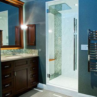 Diseño de sauna clásica renovada, grande, con armarios con paneles empotrados, puertas de armario de madera oscura, lavabo bajoencimera, encimera de cuarzo compacto, bañera encastrada, sanitario de una pieza, baldosas y/o azulejos grises, baldosas y/o azulejos de vidrio laminado, paredes azules y suelo de baldosas de porcelana