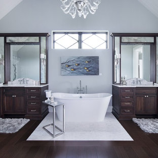 Imagen de cuarto de baño clásico renovado, extra grande, con lavabo bajoencimera, armarios con paneles empotrados, puertas de armario de madera en tonos medios, encimera de mármol, bañera exenta, sanitario de dos piezas, baldosas y/o azulejos blancos, losas de piedra, paredes grises y suelo de bambú