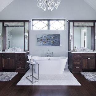 Klassisk inredning av ett mycket stort badrum, med ett undermonterad handfat, luckor med infälld panel, skåp i mörkt trä, marmorbänkskiva, ett fristående badkar, en toalettstol med separat cisternkåpa, vit kakel, stenhäll, grå väggar och bambugolv