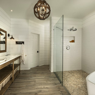 This is an example of a large arts and crafts master bathroom in Atlanta with open cabinets, light wood cabinets, a freestanding tub, a curbless shower, multi-coloured tile, mosaic tile, white walls, porcelain floors, a drop-in sink and engineered quartz benchtops.