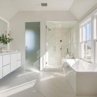 Inspiration för stora maritima vitt en-suite badrum, med släta luckor, vita skåp, ett fristående badkar, en dusch i en alkov, vit kakel, stenhäll, klinkergolv i porslin, ett undermonterad handfat, marmorbänkskiva, vitt golv, dusch med gångjärnsdörr och grå väggar