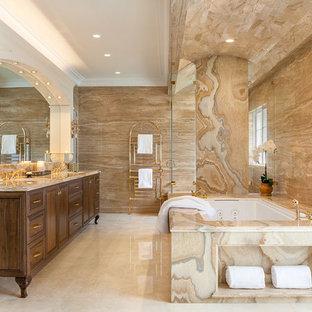Idee per un'ampia stanza da bagno padronale tradizionale con consolle stile comò, ante in legno bruno, pavimento in marmo, lavabo sottopiano, top in marmo, vasca sottopiano e piastrelle in pietra
