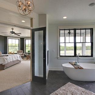 Modelo de cuarto de baño principal, de estilo de casa de campo, con bañera exenta, paredes blancas, suelo de baldosas de cerámica y baldosas y/o azulejos grises