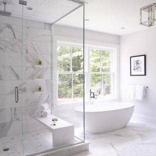На фото: огромная главная ванная комната в стиле современная классика с фасадами в стиле шейкер, темными деревянными фасадами, отдельно стоящей ванной, угловым душем, серой плиткой, белой плиткой, мраморной плиткой, белыми стенами, мраморным полом, врезной раковиной, мраморной столешницей, белым полом и душем с распашными дверями с