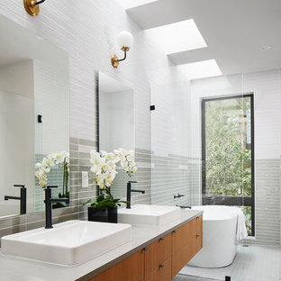 This is an example of a contemporary ensuite bathroom in Austin with flat-panel cabinets, medium wood cabinets, a freestanding bath, grey tiles, multi-coloured tiles, white tiles, a vessel sink and grey floors.
