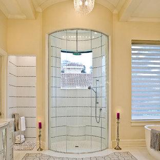 На фото: класса люкс главные ванные комнаты в средиземноморском стиле с стеклянными фасадами, серыми фасадами, отдельно стоящей ванной, открытым душем, раздельным унитазом, каменной плиткой, бежевыми стенами, полом из травертина и столешницей из оникса