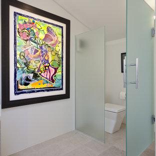 Idéer för att renovera ett stort funkis en-suite badrum, med ett undermonterad handfat, släta luckor, skåp i ljust trä, bänkskiva i akrylsten, ett fristående badkar, en kantlös dusch, en toalettstol med hel cisternkåpa, grå kakel, stenkakel, vita väggar och kalkstensgolv