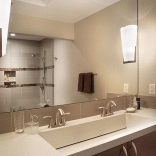 Imagen de cuarto de baño minimalista con lavabo de seno grande, armarios con paneles lisos, puertas de armario de madera en tonos medios, combinación de ducha y bañera y baldosas y/o azulejos beige