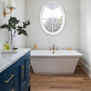Immagine di una stanza da bagno padronale costiera di medie dimensioni con ante blu, vasca freestanding, pareti beige e pavimento in legno massello medio