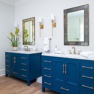 Modelo de cuarto de baño principal, clásico renovado, de tamaño medio, con armarios tipo mueble, puertas de armario azules, paredes beige, suelo de madera en tonos medios y encimera de mármol