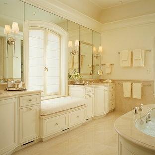 Réalisation d'une grand salle de bain principale tradition avec une baignoire encastrée, un lavabo encastré, un placard à porte affleurante, des portes de placard blanches, un plan de toilette en calcaire, un mur beige, un sol en calcaire et du carrelage en pierre calcaire.