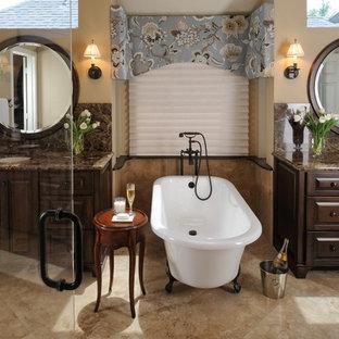 Immagine di una stanza da bagno tradizionale con vasca con piedi a zampa di leone e piastrelle in travertino