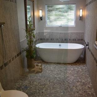 Ispirazione per una stanza da bagno padronale contemporanea di medie dimensioni con lavabo rettangolare, ante lisce, ante in legno scuro, vasca freestanding, doccia a filo pavimento, WC monopezzo, piastrelle grigie, piastrelle di ciottoli, pareti grigie e pavimento con piastrelle di ciottoli