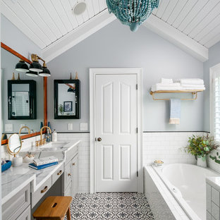 Inspiration for a transitional white tile and subway tile cement tile floor and multicolored floor drop-in bathtub remodel in Atlanta with raised-panel cabinets, gray cabinets, gray walls and an undermount sink
