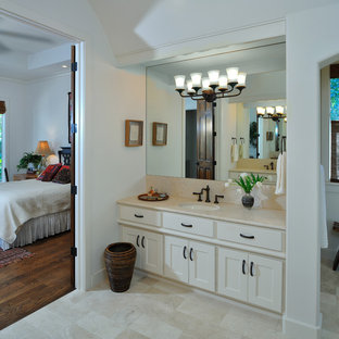Example of a tuscan beige tile and limestone tile bathroom design in Houston with beige cabinets