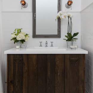 Bathroom - small farmhouse master white tile and subway tile marble floor bathroom idea in Los Angeles with a drop-in sink, flat-panel cabinets, solid surface countertops, white walls, distressed cabinets and a two-piece toilet
