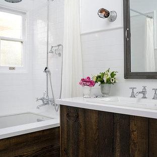 ロサンゼルスの小さいトランジショナルスタイルのおしゃれなマスターバスルーム (オーバーカウンターシンク、アンダーマウント型浴槽、シャワー付き浴槽、白いタイル、サブウェイタイル、人工大理石カウンター、分離型トイレ、白い壁、大理石の床、フラットパネル扉のキャビネット、ヴィンテージ仕上げキャビネット、シャワーカーテン) の写真